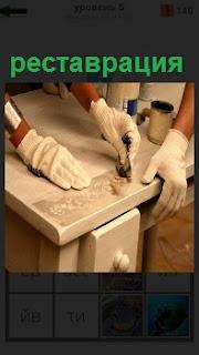 Рабочие осуществляют реставрацию инструментом поверхность светлого стола из дерева