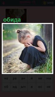 маленькая девочка сидит на дороге около дерева, плачет от обиды