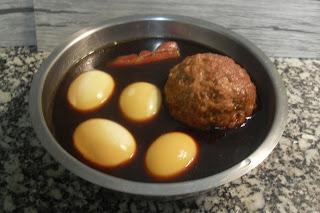 Poner en el caldo los huevos cocidos y pelados, la pelota de carne y la panceta