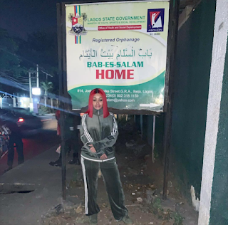 Blac Chyna standing at Lagos State Government Signboard