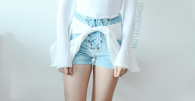 A cute outfit featuring the lace-up crushed velvet corset-style high-waisted pastel blue shorts from Home Cooked Karma (Etsy), worn with a semi-sheer white long sleeve crop top.