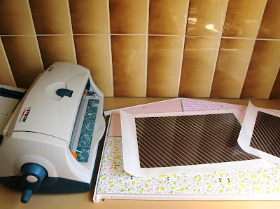 Two uncut pieces of scrapbooking paper, run though a Xyron sticker machine and sitting on the back wall of a Lundby Smaland 2015 dolls' house.