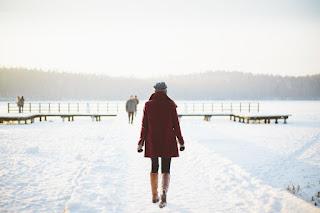 Une fille marche dans la neige au bord du lac