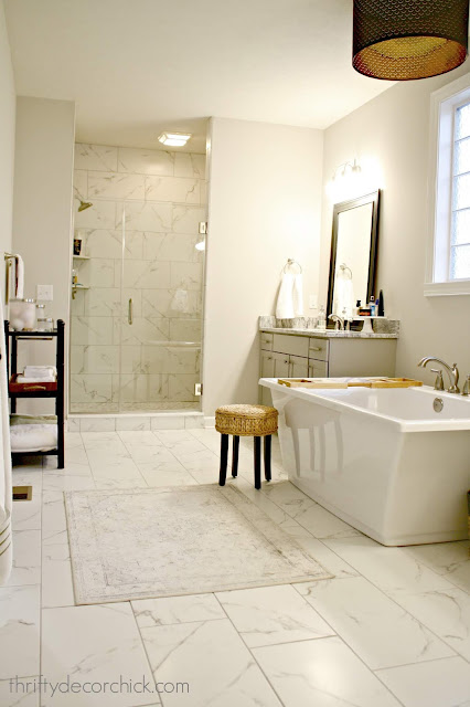 Master bath with marble tile and light gray vanities