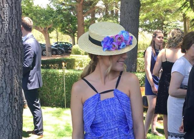 Look invitada boda con vestido corto en azul y malva, canotier de flores de copa baja y bolso abanico primer plano