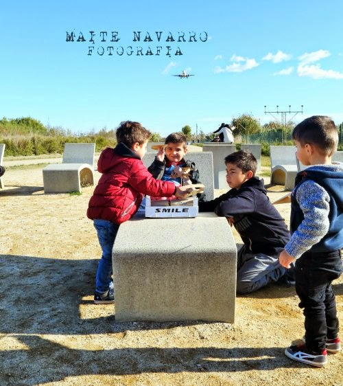 Niños observando sus aviones de cartón mientras se aproxima un avión