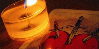 Imagen de una vela encendida encima de una baraja de espadas