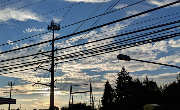 image of a bright blue sky with silvery clouds set behind the silhouette of power lines and other industry