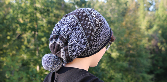 Gray and Black Slouchy Knit Scandinavian Hat Worn with Pompom Hanging Down Back