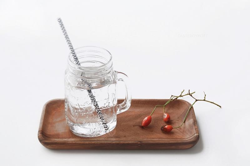 Henkelglas und Holztablett, herbstlich mit Hagebutten dekoriert. Favoriten im September. Tasteboykott