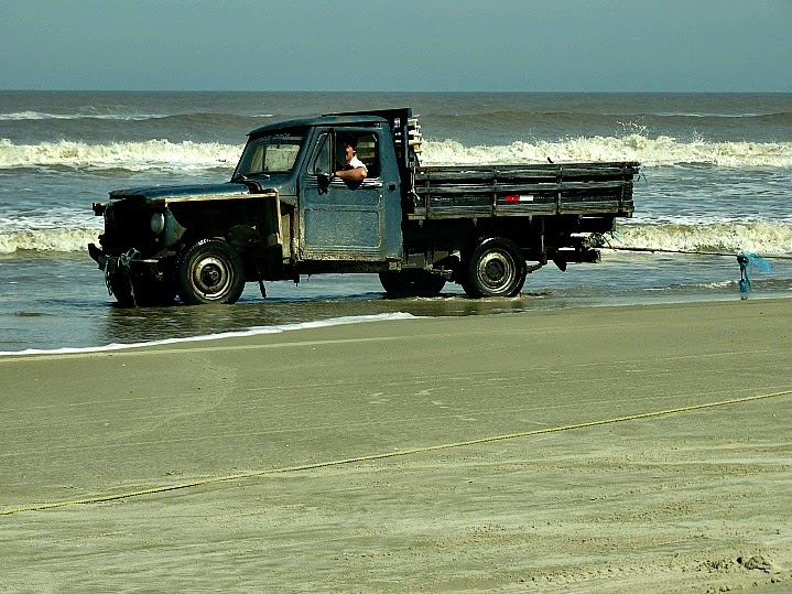 Caminhão puxa a rede de pesca, na praia, no Parque da Lagoa do Peixe, em Tavares