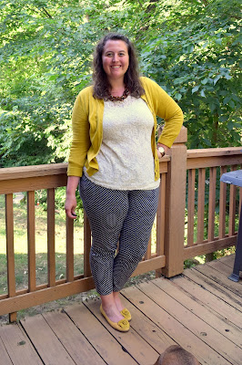 an outfit with a white lace shirt, a mustard cardigan, a tortoiseshell chain necklace, navy polka dot pants, and mustard flats