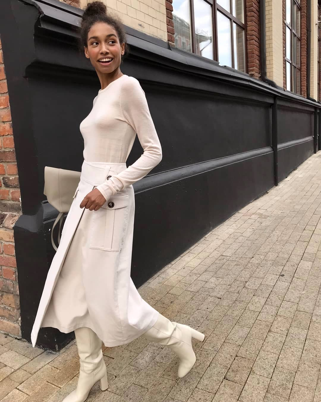Polished All-White Spring Outfit Idea — Long Sleeve Top, Utility Midi Skirt, and Knee-High Boots