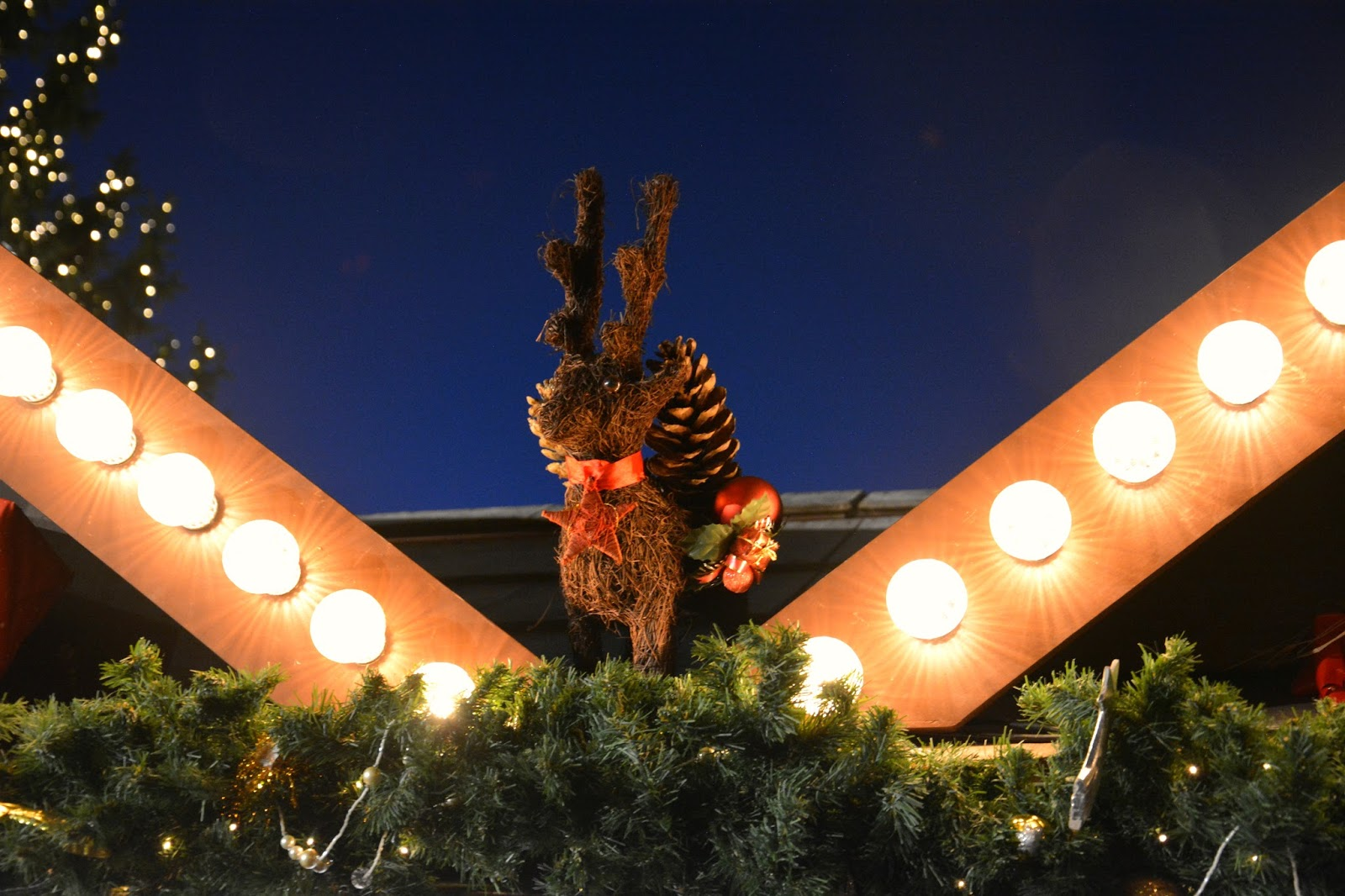 Reindeer decoration on top of huts with lights by its sides