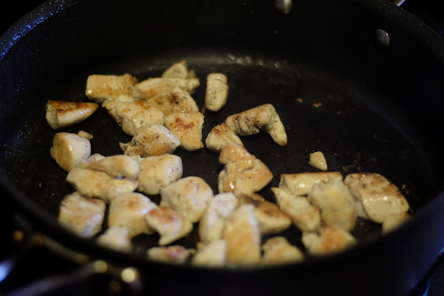 The fully cooked cubed chicken in the skillet.
