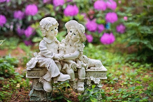 statue of two children on a bench