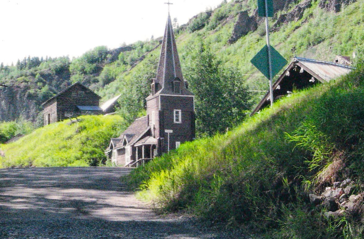 dirt road, a wooden church and a cabin