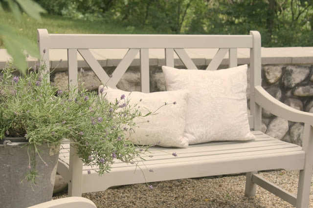 Light grey bench in pea gravel French inspired courtyard with lavender in bucket - Hello Lovely Studio