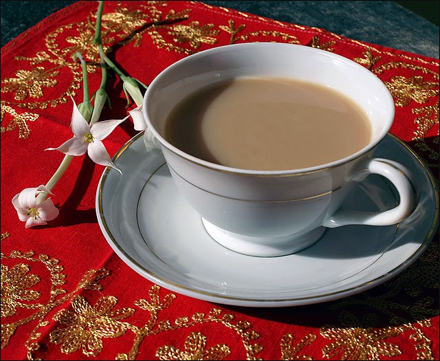 Hot masala tea in white cup with white saucer, flower on the side, red ethnic table cloth