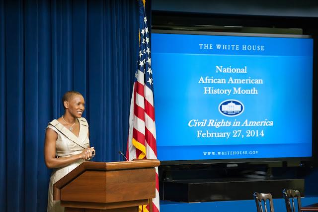 Claudia Gordon frente a un atril, bandera de USA y una proyección a un lado sobre la National African American History Month
