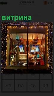 За большим стеклом освещенная витрина с представленными домашними предметами обихода