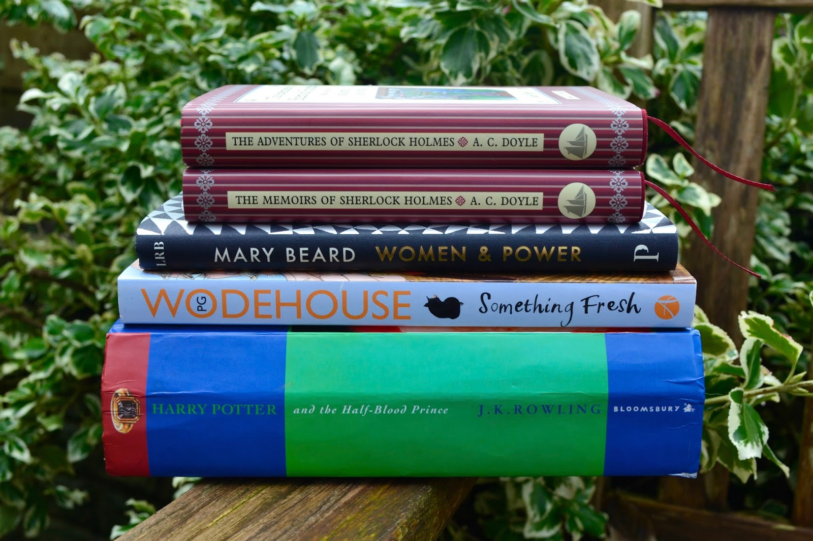 Pile of books: The Adventures of Sherlock Holmes and The Memoirs of Sherlock Holmes by Sir Arthur Conan Doyle, Women and Power: A Manifesto by Mary Beard, Something Fresh by P.G. Wodehouse and Harry Potter and the Half-Blood Prince by JK Rowling