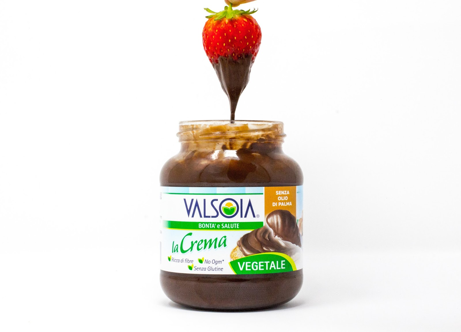 A jar of Valsoia Dairy Free Italian Chocolate Spread with a strawberry being dipped in it