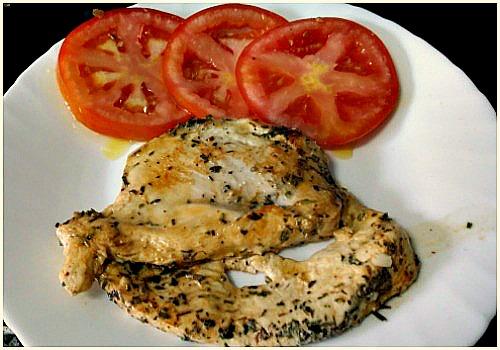 Un pollo con hierbas adobado y acompañado con tomate