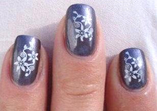 Foto de diseño de uñas con unas flores blancas y fondo azul metálico