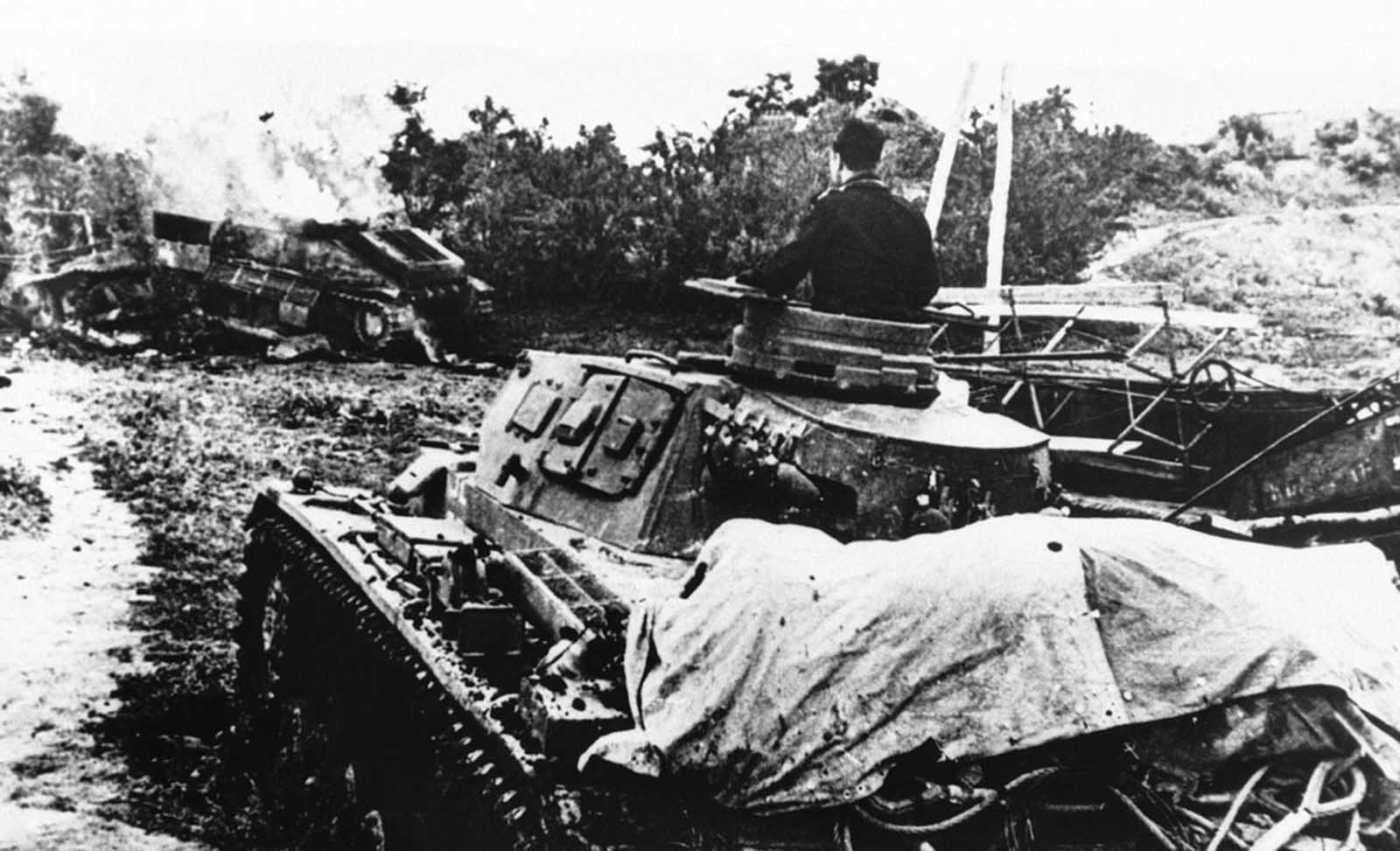 A German tank rolls up to its defeated enemy tank which burns near the edge of a patch of woods, somewhere in Russia, on October 20, 1942.