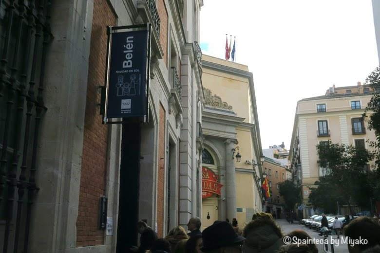 マドリード自治州の建物内のベレン人形を見ようと入口前に列に並ぶ人々