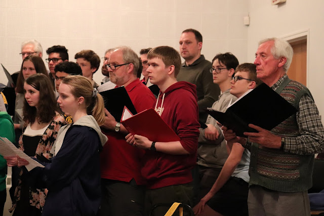 Ludwig - in red hoodie - focuses intently at a choir workshop