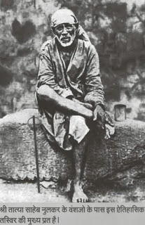 sai baba is sitting in his usual position on a stone
