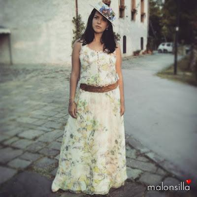 Look de boda con vestido estampado largo y canotier con flores en colores pastel y crudo
