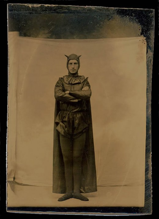 Victorian photo of a man in a devil / batman costume with snazzy tights, a cape and a bat-ear / devil horn cap. Redbad Standards and Other Stories of Hell. marchmatron.com
