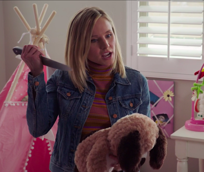 Eleanor is holding a brown teddy bear in one hand and a knife in the other. She's about to stab the bear with the knife.