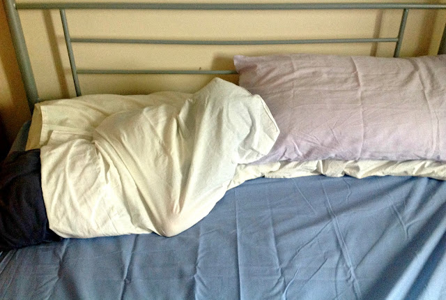 A child inside a pillowcase on a nearly-made bed.