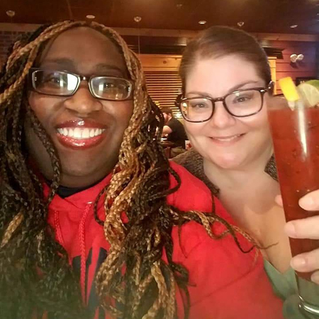 image of me with my friend K, a black woman; we are out at a restaurant, and I am holding up a drink; she is wearing a red sweatshirt and I am wearing a brown cardigan over a green cami
