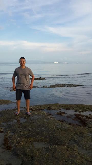 Hamparan batu karang di pantai alami muncul saat pasang surut air laut