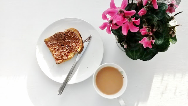 Chocolate spread on toast with tea and pink flowers