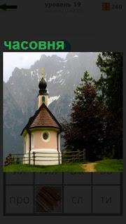 На фоне гор на природе стоит небольшая часовня с ограждением