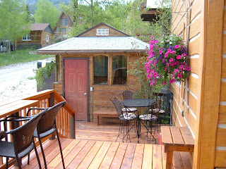 Sunny deck with chairs and a table leading to the gazebo with a hot tub, and a beautiful hanging basket with pink flowers.