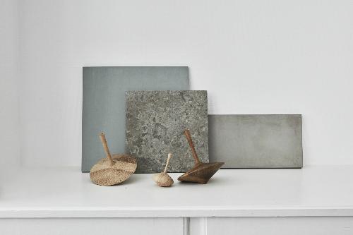 an einer Wand lehnen keine Steinplatten, davor liegen Holzkreisel