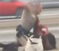 Actual Photo of Cop beating a woman on the highway, it shows the woman on the highway ground and the police officer sitting next to her with his arm in the air as he has raised it back to throw another punch
