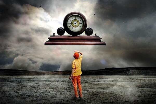 Hombre contemplando un reloj gigante en vez de aprovechar el tiempo libre