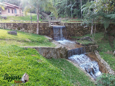 Construção do lago com muro de pedra, cascata de pedra no muro de pedra com a ponte de madeira, gramado com grama São Carlos em construção do lago em Piracaia-SP.