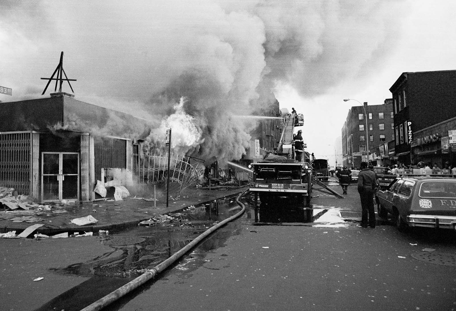 Firemen battle flames at a store in the Bronx borough of New York, one of many fires that broke out during the massive power failure that crippled the city for more than 24 hours, seen July 14, 1977. Firemen answered 1,500 alarms, 400 of which were actual fires. Forty of the fires were termed serious.
