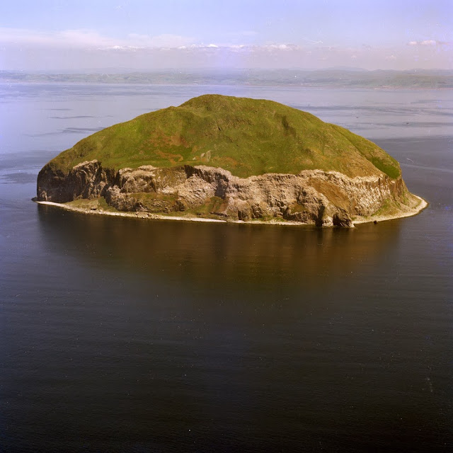 Oblique aerial view of the island of Ailsa Craig. Looking south towards the north end of the island. The island is a very prominent landmark in the Firth of Clyde formed of a microgranite boss. Ailsa Craig is formed of an arfvedsonite-aegirine-microgranite intruded by vertical dyke swarms of olivine to alkaline olivine-dolerite with basalt margins. Isotopic dating using the Rb/Sr isochron method dates the microgranite at 61.5 Ma. This makes it Tertiary in age. The remains of the castle can be seen on the skyline on the left. It was built on the orders of the Earl of Cassillis by Thomas Hamilton whose coat of arms may be seen on the walls.