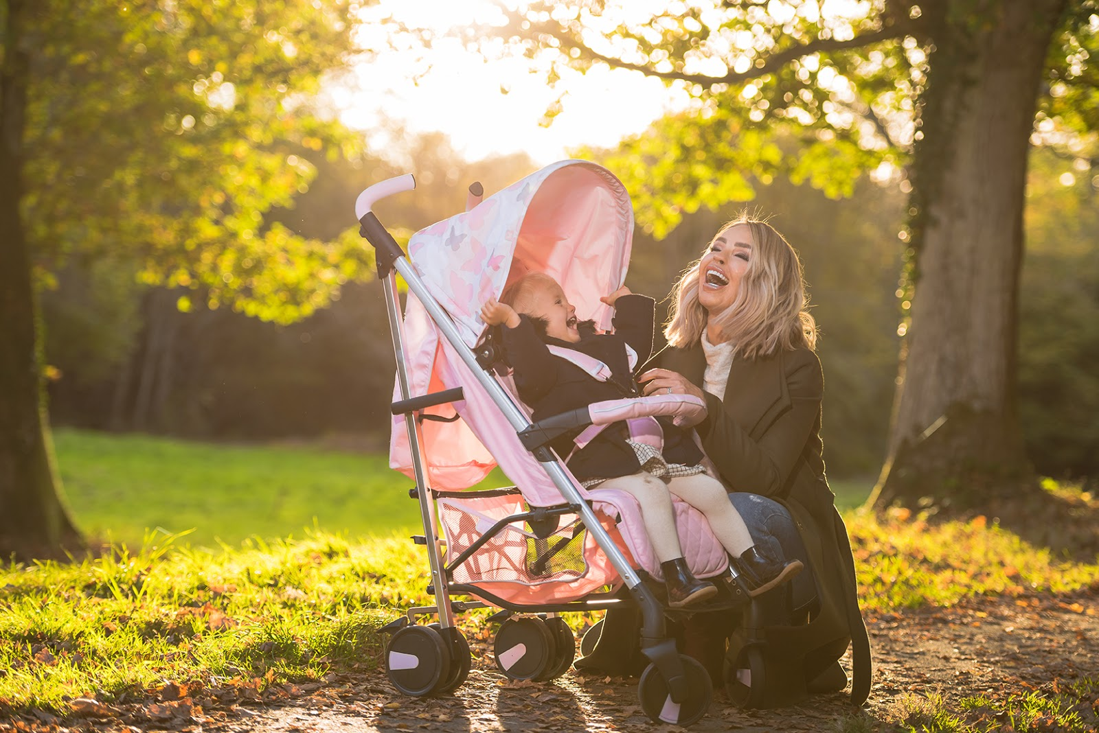 katie piper laughing next to a light pink buggy
