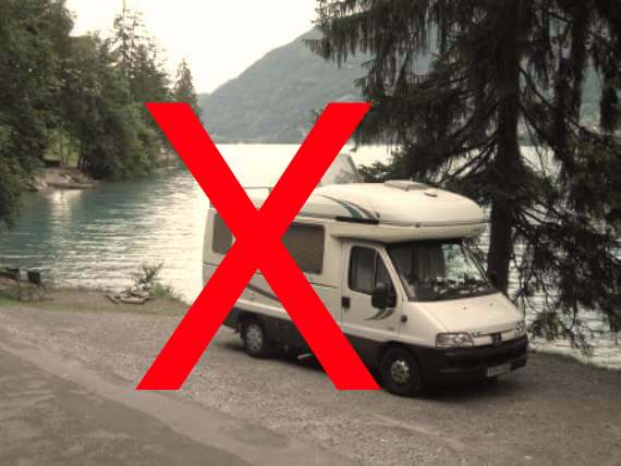 Class B van camper is by lake, has big red X over it